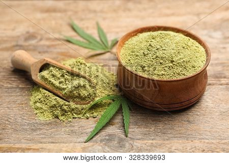 Bowl And Scoop Of Hemp Protein Powder On Wooden Table