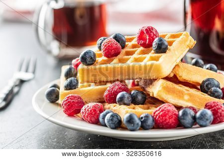 Waffles with blueberries and raspberries on plate.