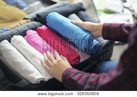 Woman Hand Pack Clothes In Suitcase Bag On Bed, Prepare For New Journey.
