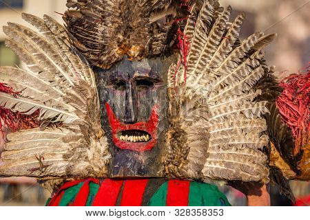 Mummers perform rituals to scare evil spirits at Surva festival at Pernik in Bulgaria. The people with the masks are called Kuker (kukeri). Wood mask with feathers and red mouth.