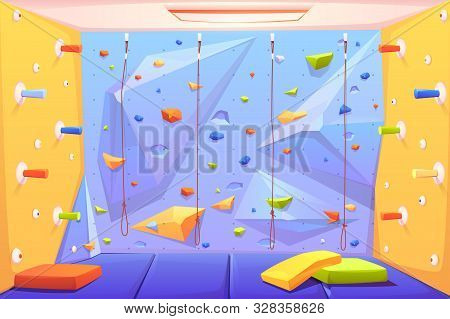 Rock Climbing Wall With Grips, Mats And Ropes For Bouldering Activity In Gym Or Recreation Area For