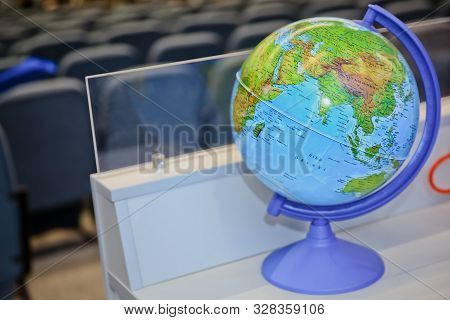 Businessman Using A Laptop With Close Up On World Globe. Global Concept. Blue Globe Against Blurred