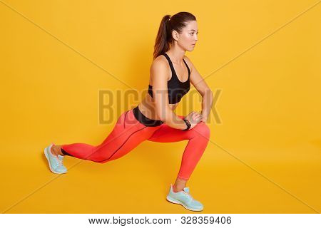 Indoor Shot Of Attractive Brunette Young Slim Woman Wearing Stylish Sports Clothing Stretching In Gy