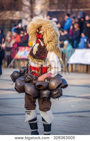Mummers perform rituals to scare evil spirits at Surva festival at Pernik in Bulgaria. The people with the masks are called Kuker (kukeri). Mask from wool and big bells.