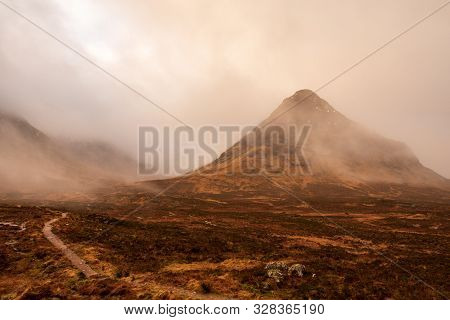 Wintery Brown Grass Fields Overlooks Low-hanging Clouds That Cover Bidean Nam Bian Mountain Covered