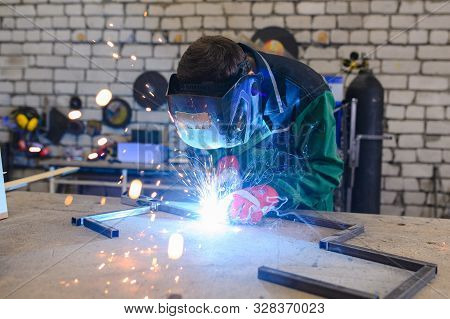 A Strong Man Is A Welder In A Welding Mask And Welders Leathers, A Metal Product Is Welded With A We