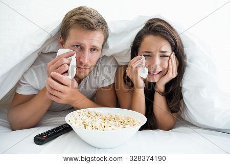 Young Couple Handsome Man And Beautiful Woman Watching Melodrama In Bed Eating Pop Corn Feeling Pitt