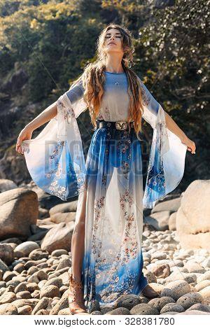 Beautiful Young Woman In Elegant Stylish Dress On Stone Beach At Sunset