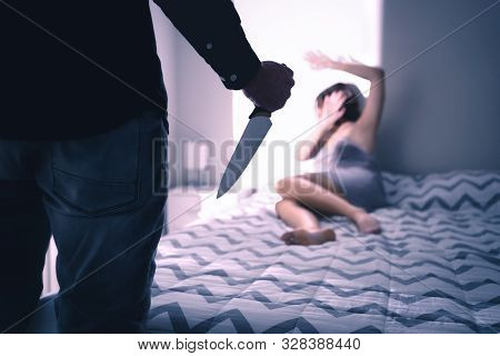 Murder, Homicide Or Halloween Concept. Murderer And Killer With A Knife. Scared Woman At Home With F