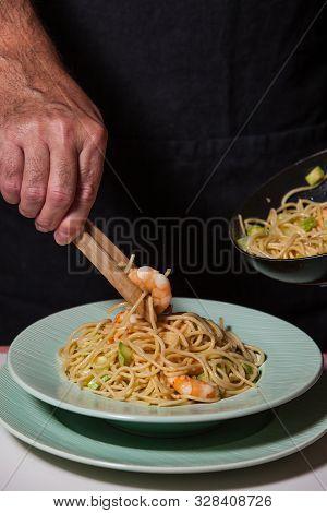 Chef Serving Homemade Italian Prawn Pasta On Plate