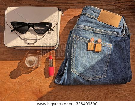 Fashion Flatlay. Jeans, White Bag, Earings, Parfume, Sunglasses, Red Lipstick On Wooden Background.