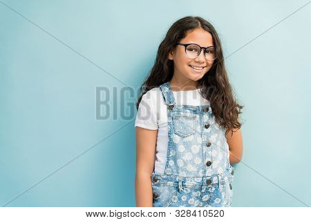 Portrait Of Smiling Preadolescent Girl Wearing Denim Overalls While Standing Against Turquoise Backg