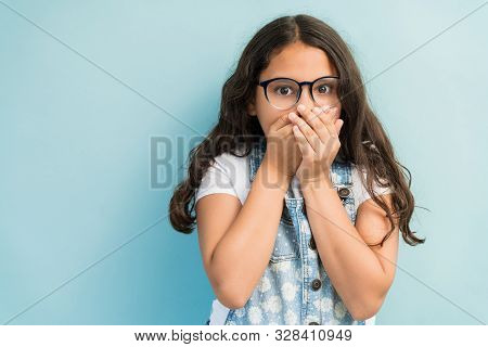 Hispanic Girl In Shock Covering Mouth With Hands While Making Eye Contact Against Plain Background