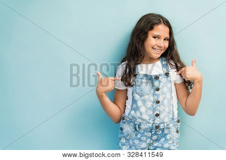 Happy Preadolescent Female Child Pointing At Herself While Against Plain Background