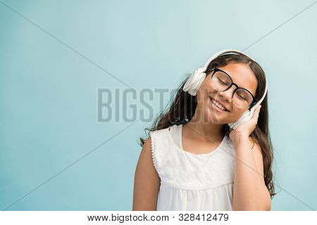 Happy Adorable Girl Listening Music Through Headphones With Eyes Closed Against Turquoise Background