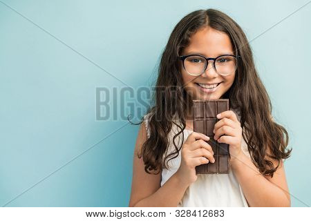 Portrait Of Latin Female Child Eagerly Waiting To Eat Chocolate Bar Against Plain Background