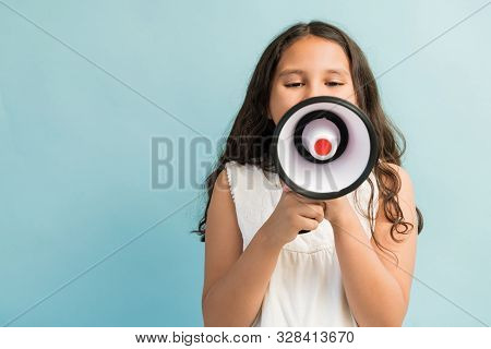 Preadolescent Girl Looking At Megaphone While Screaming Against Turquoise Background