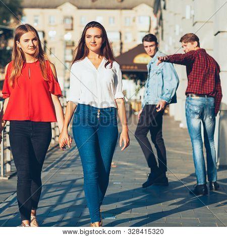 Sexual Tolerance. Judgement Mockery Shame. Men Staring At Lesbian Women Walking Holding Hands.