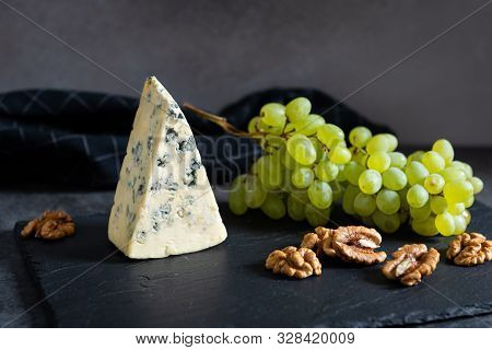 Tasty Blue Cheese Served With Green Grapes And Walnuts On A Black Stone Board. Dorblu Cheese Pieces.