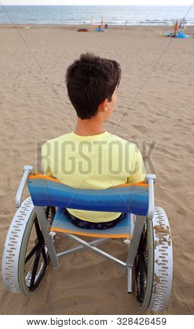 Young Boy On The Special  Wheelchair Looks At The Sea From The Sandy Beach In The Summer