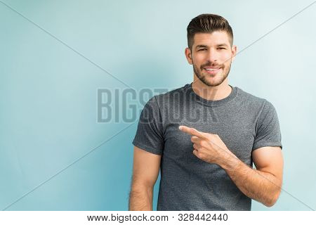 Confident Young Latin Man Wearing Gray Tshirt And Pointing At Blank Space While Making Eye Contact A