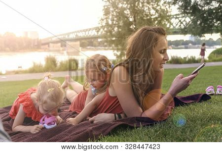 Mother With Daughters Having Picnic By River, She Chats On Smartphone And Not Looking After Children