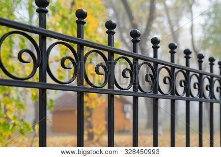 Image Of A Beautiful Decorative Cast Iron Wrought Fence With Artistic Forging. Metal Guardrail Close