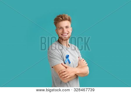 Young Man With Blue Ribbon On Turquoise Background. Urology Cancer Awareness