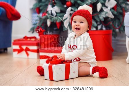 Charming Toddler Boy Holds White Christmas Gift Box With Red Ribbon. Funny Cute Baby Weared In Festi