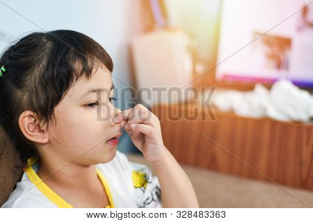 Asian Little Girl Sick With Hand Holding The Nose Get Cold And Blow Nose The Flu Season / Child Runn