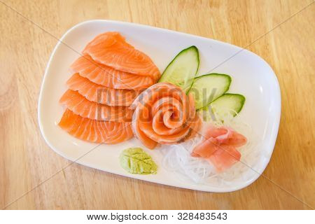 Japanese Food Raw Sashimi Salmon Fillet With Vegetable Cucumber And Wasabi In The Restaurant / Salmo