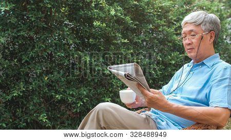 Asian Senior Men Relax At Home. Asian Senior Chinese Male Enjoy Rest Time Wear Glasses Read Newspape
