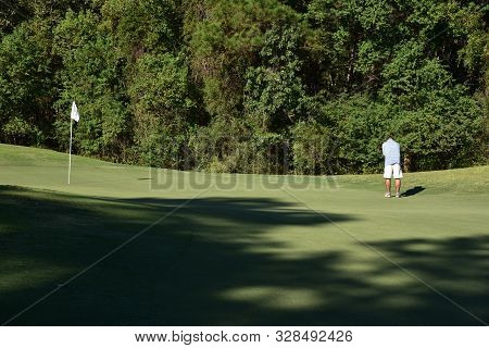 A Single, Adult, Male Lining Up A Putt On The Golf Course.