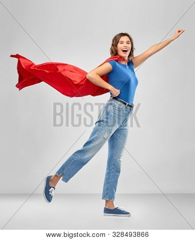 women's power and people concept - happy woman in red superhero cape making flying pose over grey background