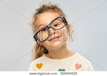 school, education and vision concept - portrait of smiling little girl in crookedly placed glasses over grey background