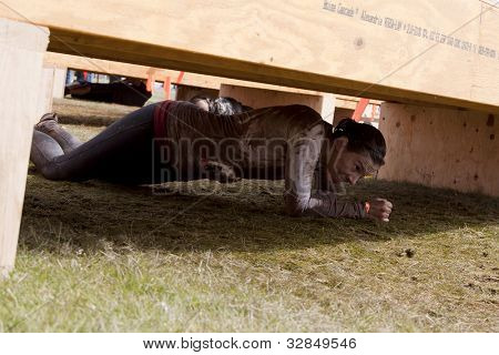 POCONO MANOR, PA - APR 28: A woman crawls under an obstacle at Tough Mudder on April 28, 2012 in Pocono Manor, PA. The course is designed by British Special Forces.
