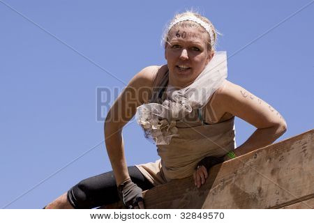 POCONO MANOR, PA - APR 29: A woman pulls herself up and over the Berlin Walls obstacle at Tough Mudder on April 29, 2012 in Pocono Manor, PA.  The course is designed by British Special Forces.