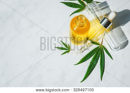 Glass Bottle With Cannabis Oil And A Test Tube With Hemp Leaves On A Marble Background. Copy Space.