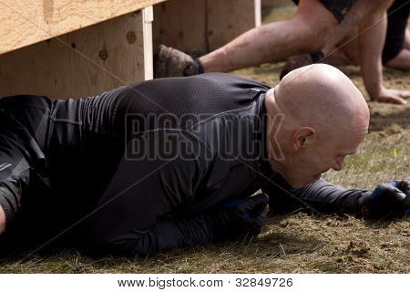 POCONO MANOR, PA - APR 28: A man crawls under an obstacle at Tough Mudder on April 28, 2012 in Pocono Manor, PA. The course is designed by British Special Forces.