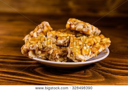 Ceramic Plate With Peanut Brittles On Rustic Wooden Table.