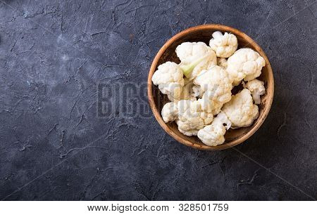 Fresh Organic Cauliflower Cut Into Small Pieces In Wooden  Bowl On Stone Background. Cauliflower Top