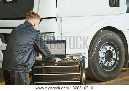 Truck repair service. Mechanic makes computer diagnostic of the semitruck