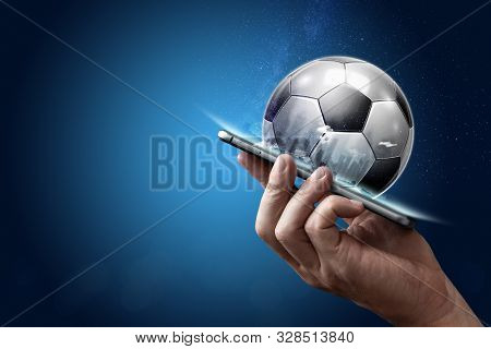 Smartphone In Hand With A 3D Soccer Ball On A Blue Background. Bets, Sports Betting, Bookmaker. Mixe