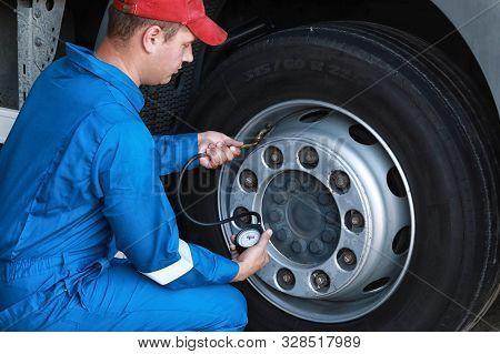 A Mechanic Checks The Tire Pressure Gauge Truck
