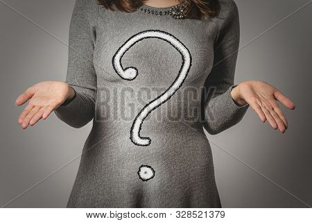 Question Mark And A Woman Who Shrugs And Spreads Her Arms On Gray Background.