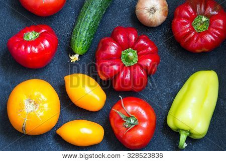 Fresh Whole Vegetables From New Harvest On Dark Blue Background. Washed Pepper, Tomatoes, Onion And