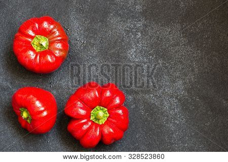 Threee Red Sweet Peppers On Dark Background With Copy Space. Natural Organic Homegrown Vegetable. To