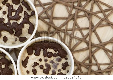 Raw Banana Ice Cream Coated With Natural Chocolate Droplets In A White Paper Cups On Table Covered W