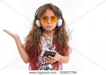 Girl In Headphones Expresses Bewilderment Ar White Background.