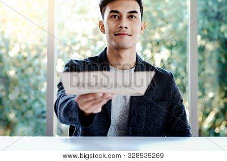 Human Resources And Job Interview Concept. Happy Young Man Sitting At The Desk Applying His Resume D